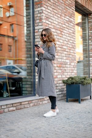 smiling elegant woman in trench coat walking and drinking coffee from paper cup . smiling woman with curly hair look at camera smile walking slow motion face sunset beautiful lady outdoor closeup cute Foto de archivo