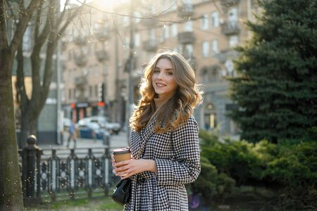 smiling elegant woman in trench coat walking and drinking coffee from paper cup . smiling woman with curly hair look at camera smile walking slow motion face sunset beautiful lady outdoor closeup cute 写真素材 - 132197524