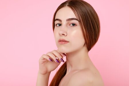 Beautiful young girl touching her perfect skin on pink background. Skin care concept. Beauty Woman Portrait with clean skin. Beauty cute fashion model with natural make up on pink background