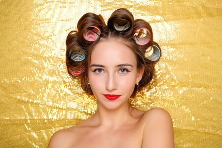 Beautiful Smiling girl in hair curlers isolated on gold. Portrait of young beautiful sexy smiling woman