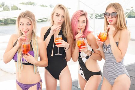 four attractive girls resting on the beach bar, drink a refreshing cocktail, laughing and having fun. The bright bathing suits and sunglasses.