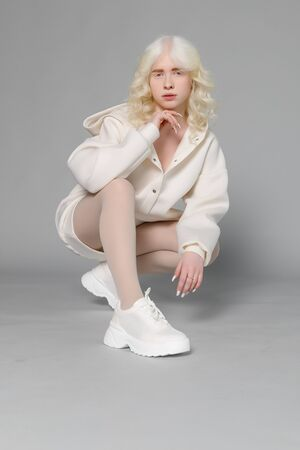 beautiful albino girl with white skin, natural lips and white curly hair wearing stylish white sweater, close up photo, copy space, beauty, fashion. Blonde girl Banco de Imagens