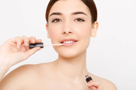 Cute girl applying lip gloss. Expressive facial expressions .Cosmetology , beauty and Spa