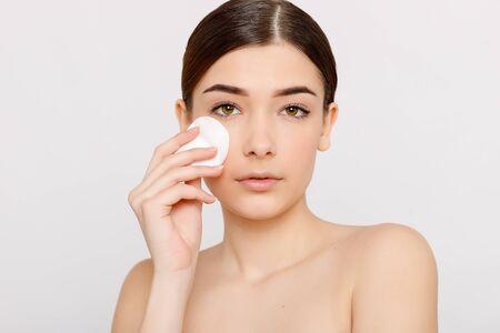 Fille fraîche en bonne santé enlevant le maquillage de son visage avec un coton. Femme de beauté nettoyant son visage avec un coton-tige isolé sur fond gris. Concept de soins de la peau et de beauté. Banque d'images