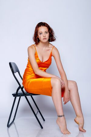 Portrait of attractive girl in orange dress in the studio. Fascinating red-haired lady. closeup portrait sitting on a chair Stock Photo