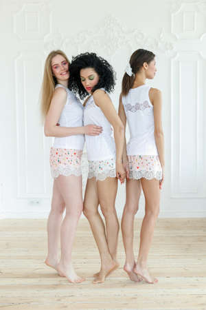 Portrait of three gorgeous multiracial young women with different types of skin. Girls standing in row and looking in opposite directions. Diverse friends concept. 版權商用圖片
