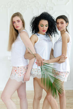 Portrait of three gorgeous multiracial young women with different types of skin. Girls standing in row and looking in opposite directions. Diverse friends concept. Palm branch