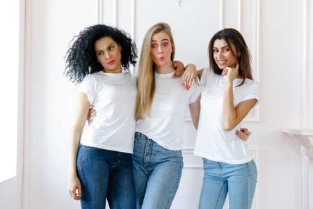 Portrait of three seductive multiethnic women standing together and smiling at camera isolated over white background