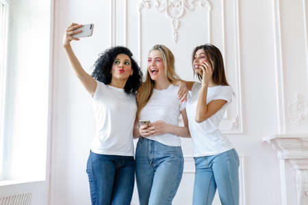 Portrait of three seductive multiethnic women standing together and smiling. Three beautiful smiling girlfriends taking selfie with mobile phone. taking self portrait.