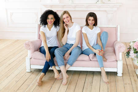 friendship and happiness concept - three girlfriends having a talk at home. Three happy funny multi ethnic ladies best friends laughing having fun, pretty diverse women wear white t-shirts and jeans 版權商用圖片