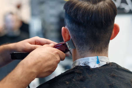 Hairstyling process. Close-up of a barber drying hair of a young bearded man. Young man in barber shop sits in an armchair. Barber cuts his hair with a trimer