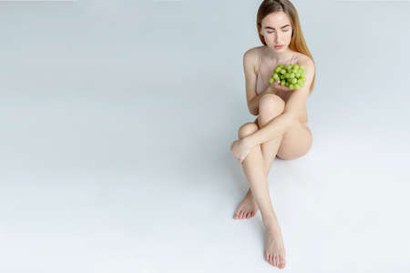 Lady Wearing Beige Swimsuit Model Isolated. Woman holds grapes in the chest