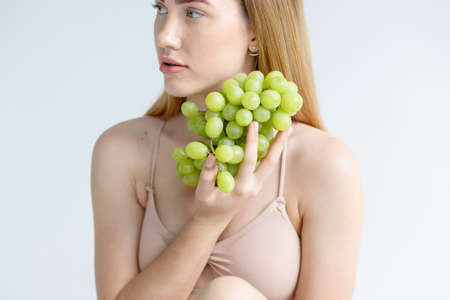 Lady Wearing Beige Swimsuit Model Isolated. oman holds grapes in the chest