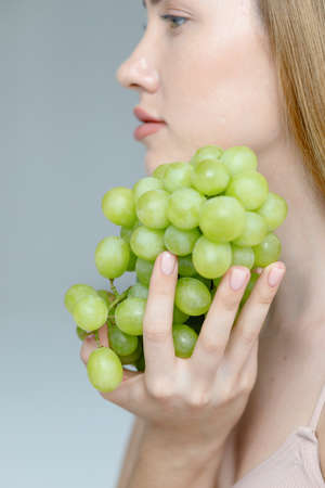 Lady Wearing Beige Swimsuit Model Isolated. Woman holds grapes