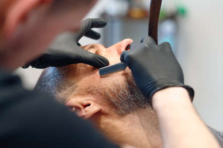 Professional barber shaves customer beard with straight razor. Beard cut with old-fashioned blade at barbershop. Handsome macho man getting his beard shaved in studio. Close-up shot.