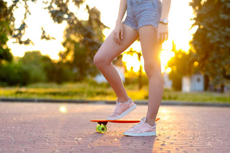 Beautiful active brunette girl with long hair wearing top, blue denim shorts and stylish pink sneakers posing on sunset background. Girl holding a orange skate with green wheels. legs close up