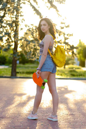 Beautiful active brunette girl with wearing top, blue denim shorts and stylish pink sneakers posing on sunset background. Girl holding a orange skate with green wheels. girl is standing with her back 写真素材