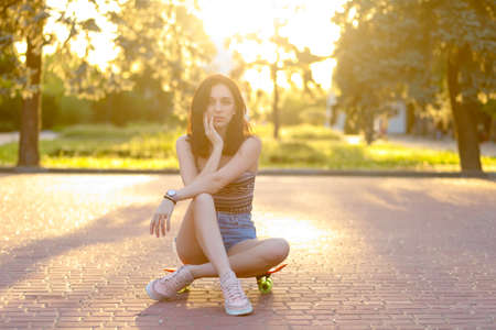 Beautiful active brunette girl with long hair wearing top, blue denim shorts and stylish pink sneakers posing on sunset background. Girl holding a orange skate with green wheels. girl sitting