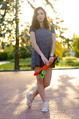 Beautiful active brunette girl with long hair wearing top, blue denim shorts and stylish pink sneakers posing on sunset background. Girl holding a orange skate with green wheels.