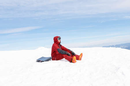 winter, leisure, sport and people concept - snowboarder sits high in the mountains on the edge of the slope and looks into the distance.
