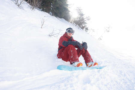 winter, leisure, sport and people concept - Man snowboarding in the mountains. Snowboarder resting on mountain top on a background of blue sky. Ski resort. Standard-Bild