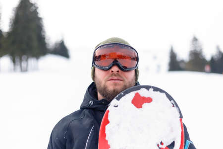 winter, leisure, sport and people concept - Snowboarder in helmet standing at the very top of a mountain and holding his snowboard behind his back
