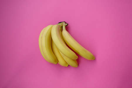 Single banana on a pink background with strong shadow. lot of bananas