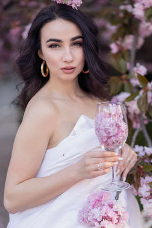 people, rest, comfort and leisure concept - Young woman through the evening streets wrapped in a blanket. Beautiful young girl in the park and a flowering tree sakura holding a glass with petals