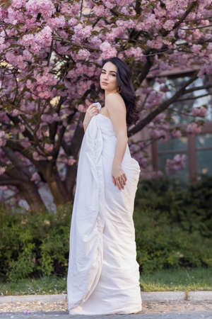 people, rest, comfort and leisure concept - Young woman through the evening streets wrapped in a blanket. Beautiful young girl in the park and a flowering tree sakura Zdjęcie Seryjne