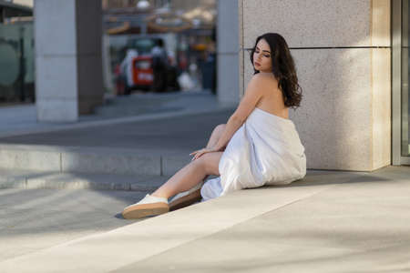 people, rest, comfort and leisure concept - Young woman through the evening streets wrapped in a blanket. sitting on the steps of the mall