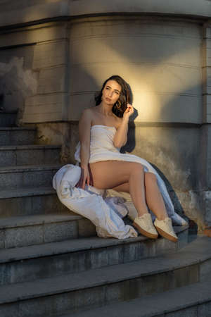 people, rest, comfort and leisure concept - Young woman through the evening streets wrapped in a blanket. Portrait of young woman sits on the steps of an old building at dawn
