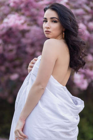 people, rest, comfort and leisure concept - Young woman through the evening streets wrapped in a blanket. Beautiful young girl in the park and a flowering tree sakura 免版税图像 - 157890030