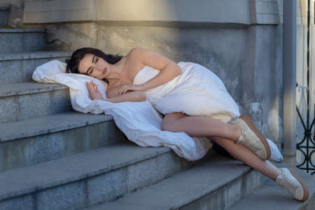 people, rest, comfort and leisure concept - Young woman through the evening streets wrapped in a blanket. Portrait of young woman sleeping of the city in open air against the background dawn.