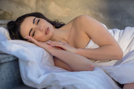 people, rest, comfort and leisure concept - Young woman through the evening streets wrapped in a blanket. Portrait of young woman sleeping of the city in open air against the background dawn. 免版税图像 - 157890087