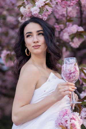 people, rest, comfort and leisure concept - Young woman through the evening streets wrapped in a blanket. Beautiful young girl in the park and a flowering tree sakura holding a glass with petals 免版税图像 - 157890092