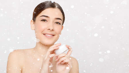 snow, winter, christmas, people, beauty concept - Beauty portrait of girl with perfect make-up. Holding cream, some cream on finger. Beauty salon. Head and shoulders. 16: 9 panoramic format. Standard-Bild
