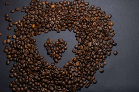 heap of coffee beans on black background. Coffee beans pile isolated on black background. Culinary coffee background. heart shaped coffee beans top view 免版税图像