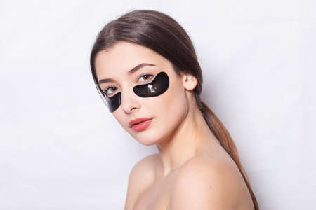 Eye patch, Beautiful Woman With Natural Makeup And Black Hydro Gel Eye Patches On Facial Skin. Girl in a white shirt, dark hair gathered neatly in a ponytail, under eye black patches for skin care. Stock Photo