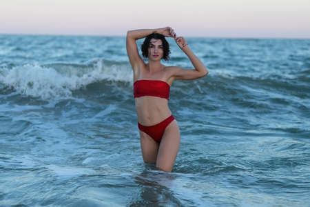 Summertime recreation concept. Beautiful young woman with fit trained slim body wearing red swimwear bikini poses on a sandy beach. Fashion female model near the sea.