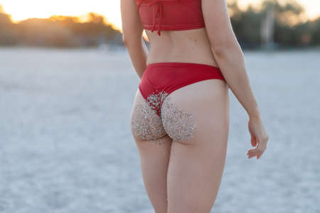 Rear view of a sexy tattooed young girl in a red swimsuit posing on the beach. Beautiful blonde woman with long hair relaxes by the ocean. The concept of a sports model, swimwear