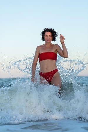 Sexy back of a beautiful woman in red bikini on sea background.