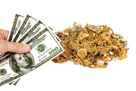 scrap gold: Everyone needs a little extra money   Sell some of your unwanted jewelry for cash  Hand holding  100 dollar bills with pile of gold jewelry in the background   Isolated on white   Studio shot  Stock Photo