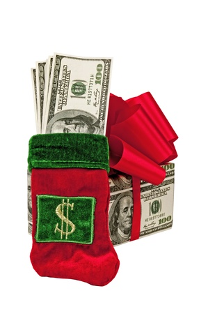 A Christmas stocking filled with money leans against a Christmas present made of money   Isolated on white  photo