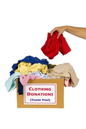 Putting clothes in a clothes donation box  Studio shot  Isolated on white Stock Photo - 17109501