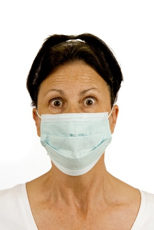 protective: A surgical mask is used to protect from germs   This woman is fearful of catching something like the flu, etc   Isolated on white  Studio shot  Stock Photo