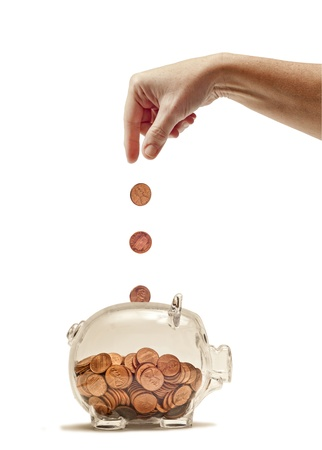white piggy bank: Great idea or concept for feeding the piggy bank or just saving money   Many pennies filling up a clear piggy bank   Hand shown dropping pennies in   Isolated on white   Studio shot