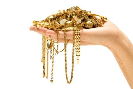 Mano que sostiene el oro hermoso del oro listo para vender Pila de joyas en la mano aislados en blanco Studio shot