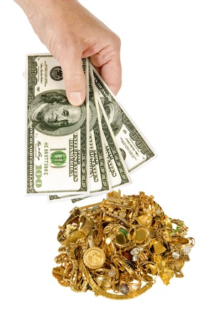Hand holding $100 dollar bills with pile of gold jewelry in the background.   on white.  Studio shot. Stock Photo - 17223615