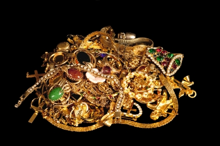 scrap heap: Here is a beautiful picture of a pile of gold jewelry that was shot on a black cloth background  Stock Photo