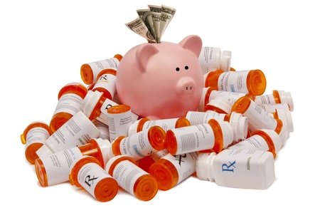 A piggy bank sits atop a pile of pill bottles with funds in his hole to pay for the increasing prices of medicines